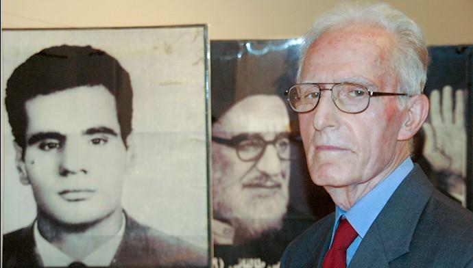 محمد سیدی کاشانی در کنار تصویری از محمد حنیفنژاد، بنیانگذار کبیر مجاهدین