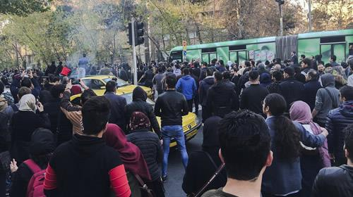 University students attend a protest inside Tehran University while a smoke grenade is thrown by anti