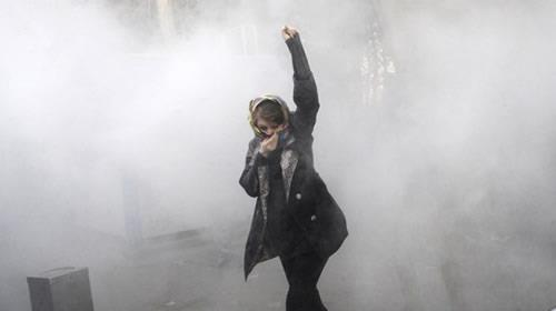 An Iranian demonstrator at the University of Tehran in a tear gas with a fist testifies that resistance to oppression continues.