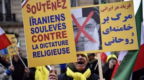 """Protesters hold placards reading """"Support Iranians risen up against the religious dictatorship"""