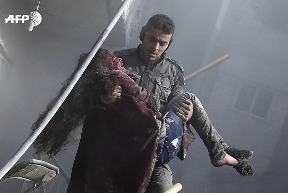 A rescuer emerge from the rubble carrying a child
