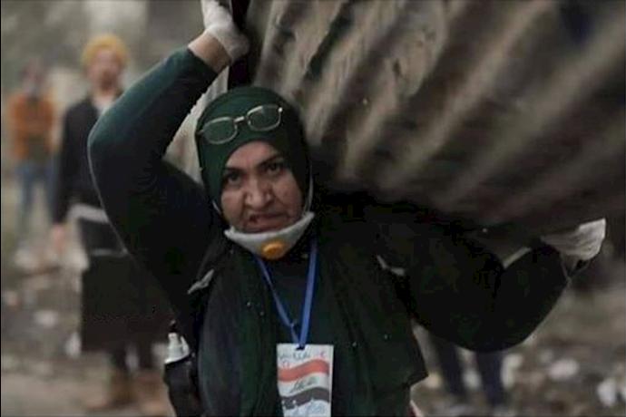 یک خانم عراقی در حال انتقال چینکو برای مسدود کردن مسیرها