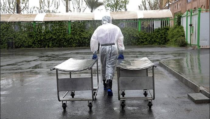 یکی از کارکنان بهشت زهرا در حال انتقال برانکارد برای انتقال قربانیان کرونایی